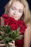 Blond smelling roses Stock Photos