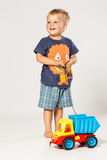Blond smiling boy playing with a plastic car, Royalty Free Stock Images