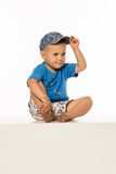 Blond smiling boy sitting on the table wearing baseball cap. White Royalty Free Stock Images