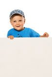 Blond smiling boy sitting on the table wearing baseball cap. White Royalty Free Stock Photography