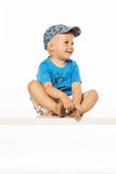 Blond smiling boy sitting on the table wearing baseball cap Royalty Free Stock Image