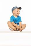 Blond smiling boy sitting on the table wearing baseball cap. White bacgound Royalty Free Stock Photos