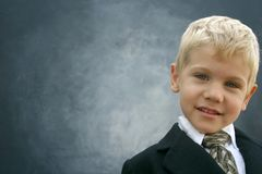 Blond smiling business boy. Adorable smiling blond boy wearing suit and tie in front of gradient gray background with room for copy Royalty Free Stock Images