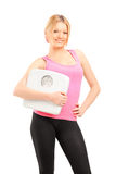 Blond smiling female athlete holding a weight scale Stock Photos