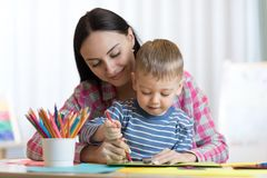 Blond smiling little boy hold in hand pencil drawing something together with mom. Blond smiling child little boy hold in hand pencil drawing something together Stock Images