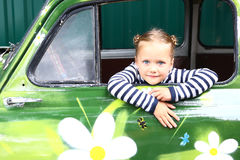 Blond smiling preteen girl in old painted car Royalty Free Stock Photos