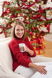 Blond smiling woman in front of Christmas tree Royalty Free Stock Images