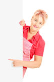 Blond smiling woman wearing an apron and gesturing on a panel Stock Image