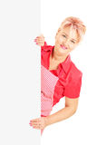Blond smiling woman wearing an apron and holding a panel Stock Image