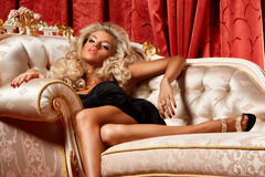 Blond on a sofa. Alluring blond relaxing on a sofa in luxury interior Stock Images