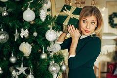 Blond, Spaß nahe dem Weihnachtsbaum mit einem Geschenk in den Händen habend Lizenzfreie Stockbilder