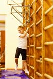 Sports seven-year-old boy in a white t-shirt and black shorts is engaged on the Swedish wall in the gym stock photos