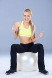 Blond sporty woman sitting on fitness ball Stock Photos