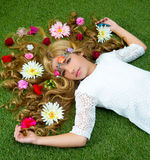 Blond spring girl with flowers on hair over grass Stock Photography