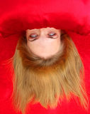 Blond with Strange Eyes. Upside down head of female with strange white eyes. Face is hidden under red pillow and background is red cloth stock photography