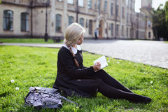 Blond student girl in schoolyard Royalty Free Stock Photos