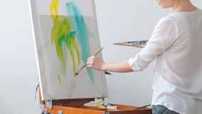 Blond student learning basic painting skills. Enjoyment of art in everyday experiences stock footage