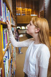 Blond student looking for book in library shelves Stock Photo