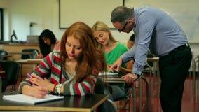 Blond student som frågar hennes föreläsare en fråga i grupp lager videofilmer