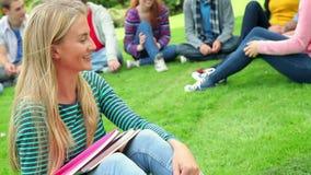 Blond student som ler på kameran med vänner bak henne på gräs lager videofilmer