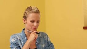 Blond student som tar anmärkningar i klassrum arkivfilmer