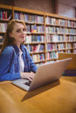 Blond student using laptop in library Stock Image