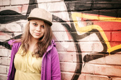 Blond stylish teenage girl stands near urban wal Royalty Free Stock Photos