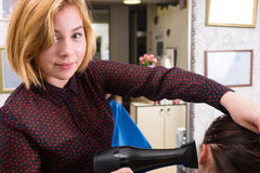 Blond Stylist Drying Hair of Woman with Blow Dryer Royalty Free Stock Photos
