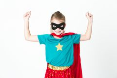 Blond supergirl with black mask and red cape posing in front of white background. Beautiful blond supergirl with black mask and red cape posing in front of white stock photography