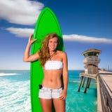 Blond surfer teen girl holding surfboard on beach stock photo
