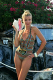 Blond swimsuit model standing in front of vintage car Stock Photo