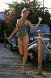 Blond swimsuit model standing in front of vintage car Royalty Free Stock Images