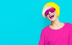 Blond szczęśliwa dziewczyna z elegancką nakrętką i okularami przeciwsłonecznymi na jaskrawym bac Zdjęcie Royalty Free