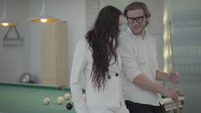 Portrait blond bearded man and his girlfriend talking near the billiard table. Confident man in white shirt explains to