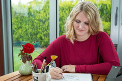 Blond teckning och skissa för kvinnakonstnär Arkivbild
