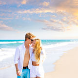 Blond teen couple walking together in the beach Royalty Free Stock Photos