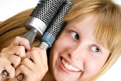 Blond teen girl with hair brushes Stock Photos
