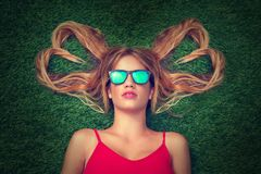 Blond teen girl with hair heart shapes lying. Down on turf with sunglasses Stock Photography