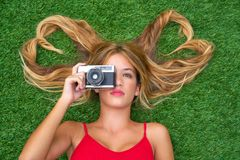 Blond teen girl with hair heart shapes lying. Down on turf with vintage photo camera Royalty Free Stock Photos