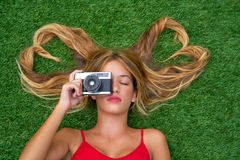 Blond teen girl with hair heart shapes lying. Down on turf with vintage photo camera Royalty Free Stock Images