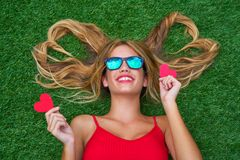 Blond teen girl with hair heart shapes lying. Down on turf Royalty Free Stock Images