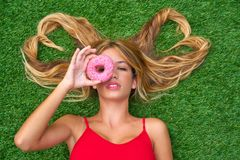 Blond teen girl with hair heart shapes lying. Down on turf with donuts on eye Stock Photo