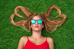 Blond teen girl with hair heart shapes lying. Down on turf with sunglasses Royalty Free Stock Image