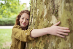 Blond Teen Girl Hugging Huge Tree Trunk Royalty Free Stock Photos