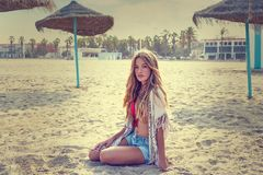 Blond teen girl sit on the beach sand. Near thatch umbrellas Stock Photography