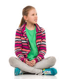 Blond Teen Girl Sitting Legs Crossed And Looking Away Royalty Free Stock Images