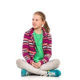 Blond Teen Girl Sitting Legs Crossed And Looking Away Royalty Free Stock Photography