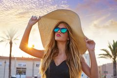 Blond teen girl sunglasses and pamela sun hat. At palm tree sunset royalty free stock photos