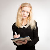 Blond Teen Girl Writing Notes On Notepad Stock Photography