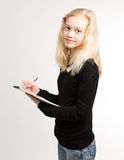 Blond Teen Girl Writing Notes On Notepad Royalty Free Stock Image